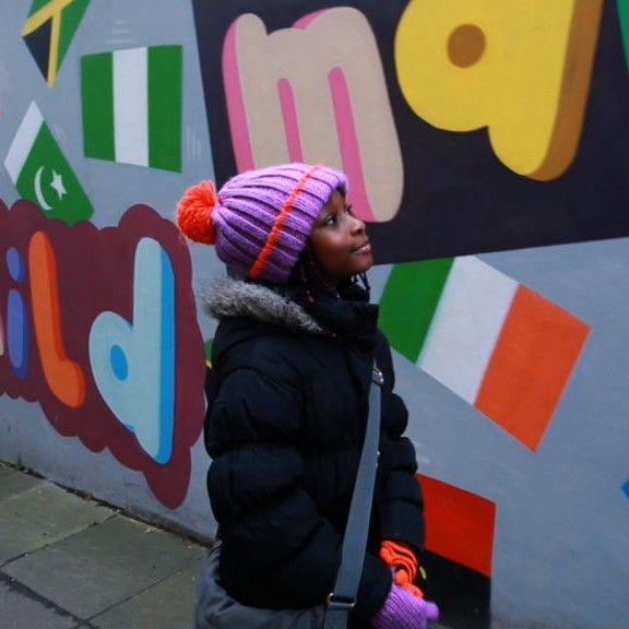 Young girl walking past wall with lots of different national flags painted on the wall