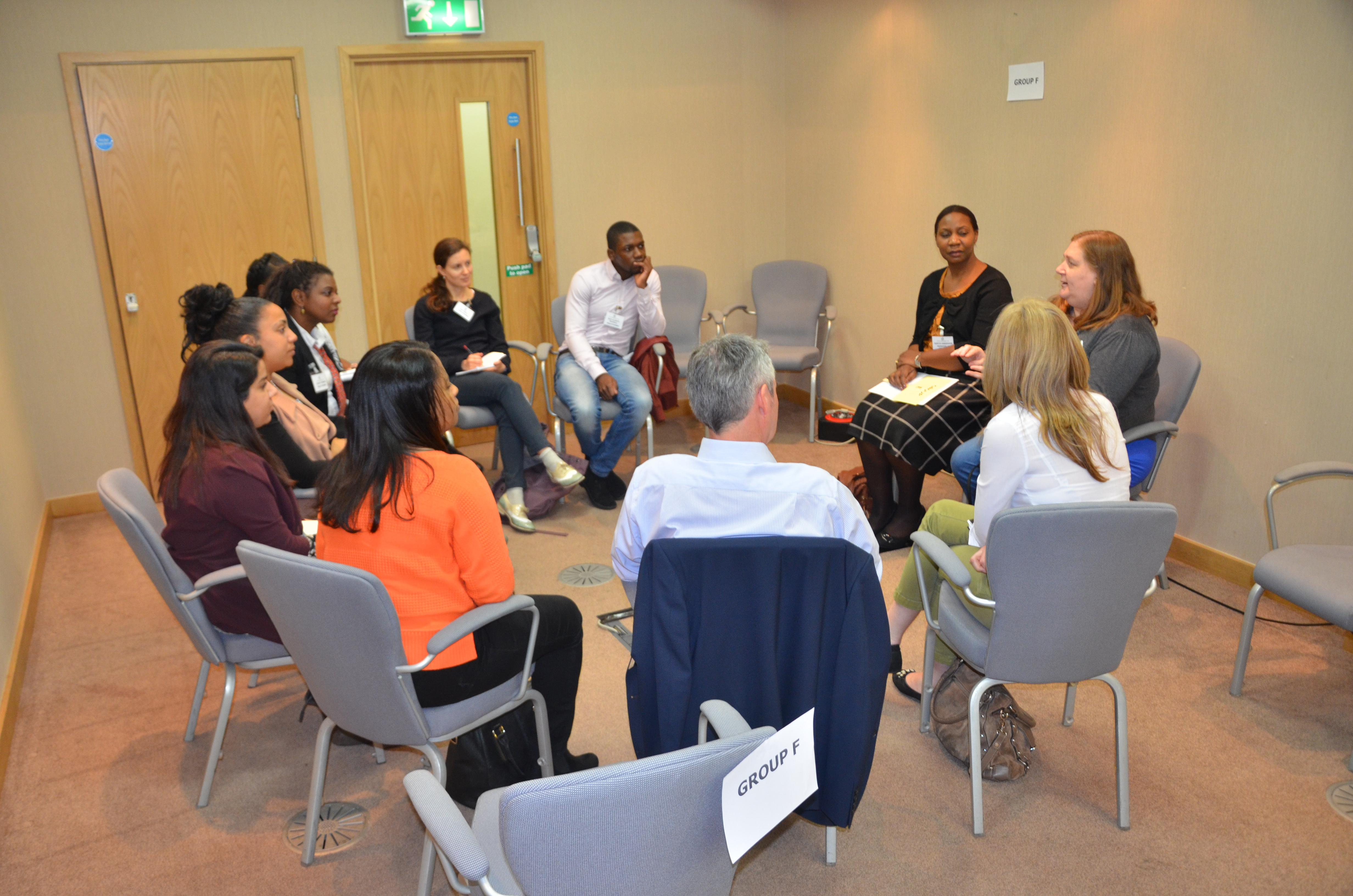 Another group of practitioners gather in a circle on chairs