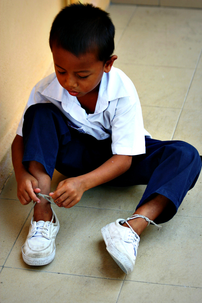 A school boy ties his shoelaces