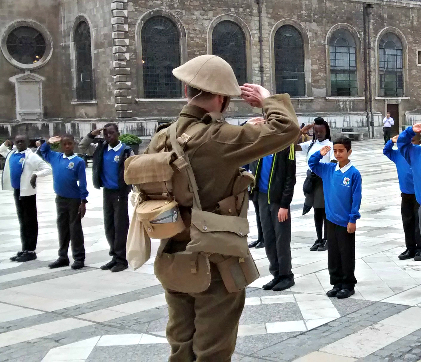Man in WWI soldier's uniform salutes some children who salute back.