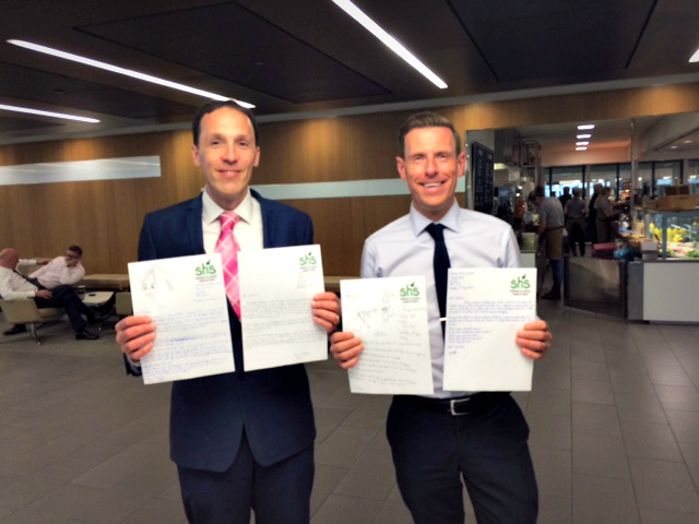 Two employees hold up their letters