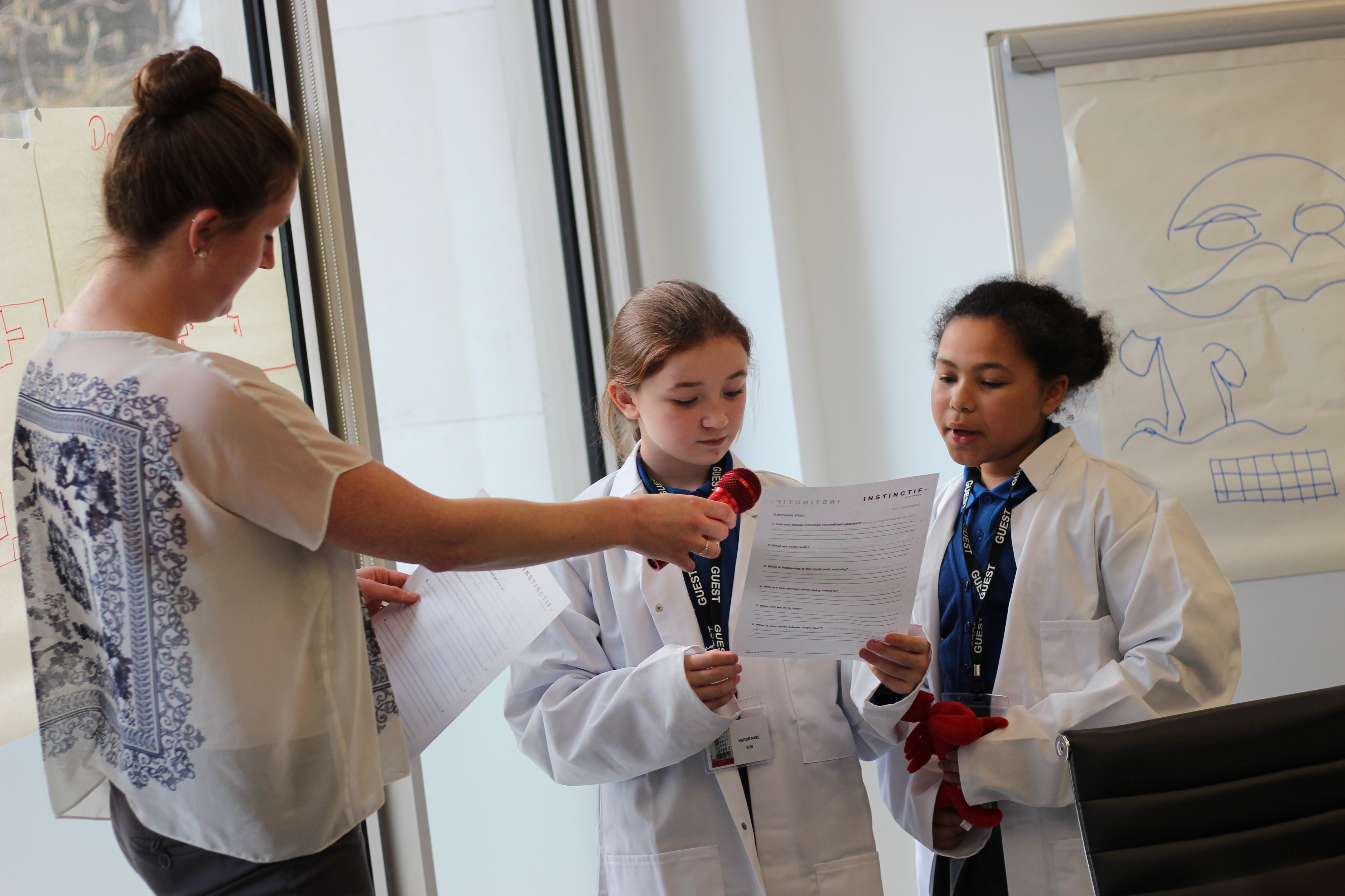 An Instinctif employee pretends to interview two girls dressed as science experts in lab coats