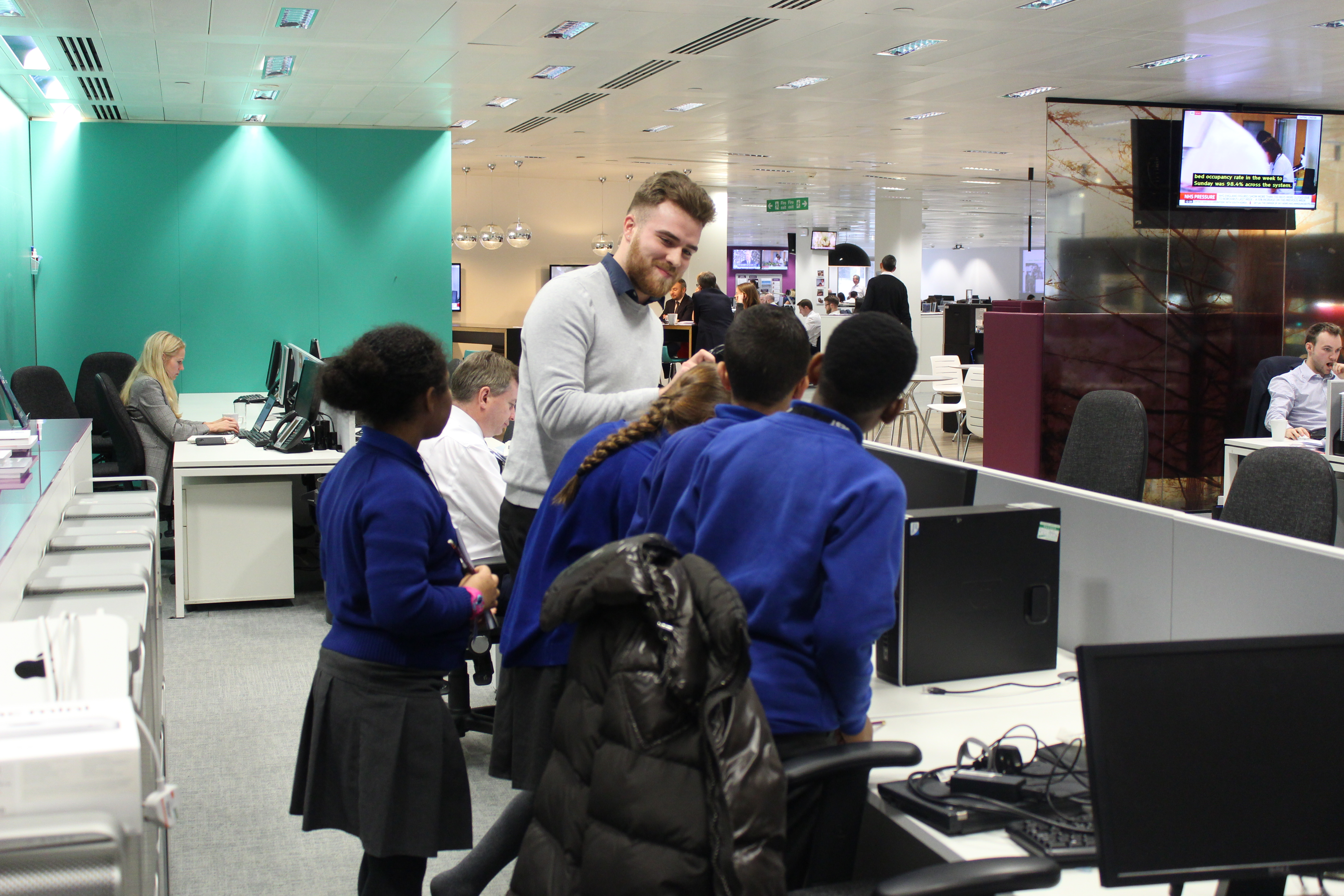 Instinctif employees teaches a group of children how to build a computer