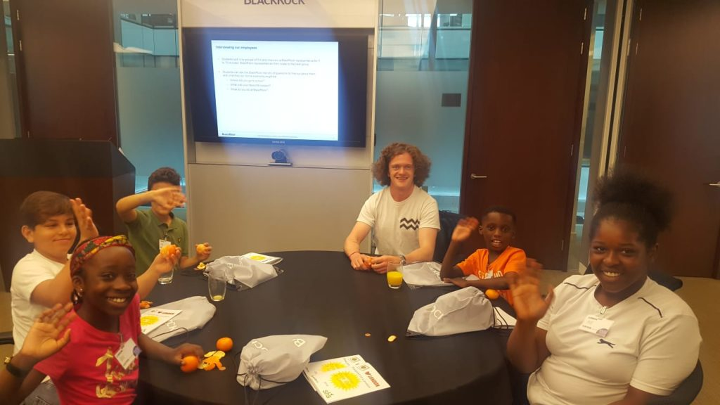 Children and an SHS volunteer from BlackRock sit around a table in the BlackRock conference room eating satsumas