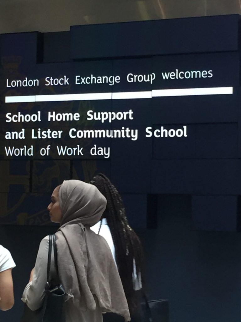 Young women walk past the welcome sign at the London Stock Exchange 'World of Work day'